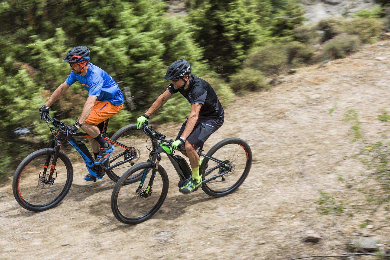 Zwei E-Mountainbiker fahren von rechts oben berg ab